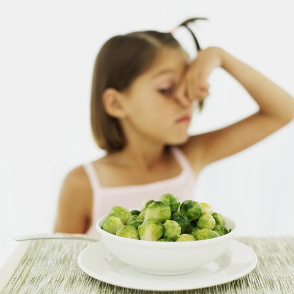 girl sticking nose up at brussels sprouts
